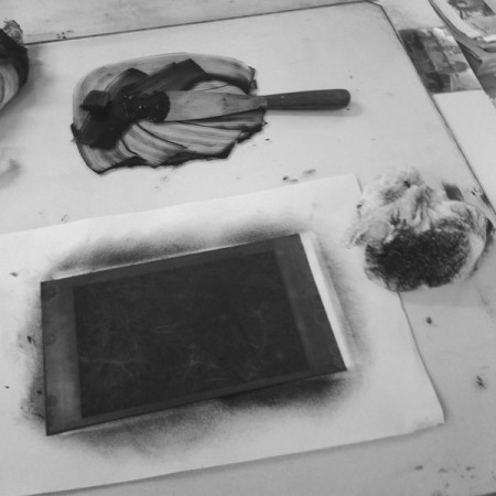 The plate being inked before taken through a print press