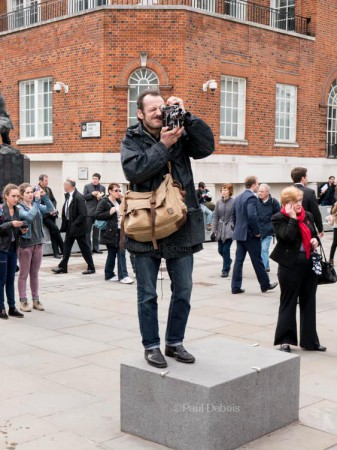 Photographer standing on a statue plinth near St Paul's Cathedral