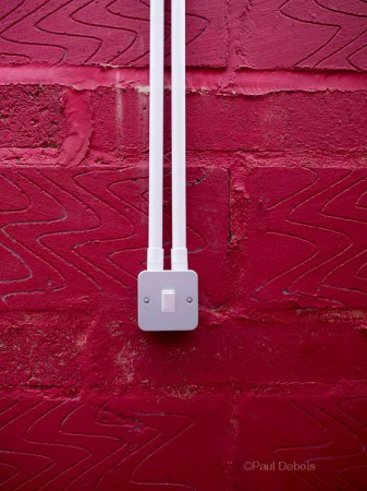 Light switch on painted red brick wall